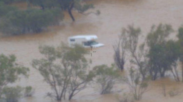 The tourists were stranded by floods when a grazier came to the rescue in his helicopter.