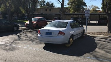 A Perth real estate agent and a prospective buyer had their cars' wheels clamped – despite parking in the designated visitors' bays.