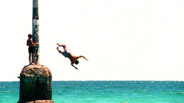 Swimmers jump off Cottesloe's famous beach pylon. Photo: AFR