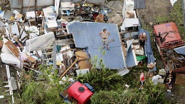 In this photo a resident stands on his roof after Cyclone Larry destroyed his property in Innisfail in March 2006.