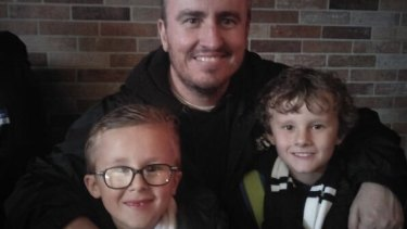 Collingwood fan Daniel Slattery with his sons Callum, 11, and Mitchell, eight.