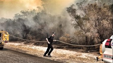Queensland police helping firefighters run a line the fight the Kinkuna Waters bushfire, south of Bundaberg, on Friday.