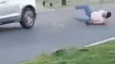 Dramatic footage shows a man hit by a car during a wild street brawl west of Brisbane.
