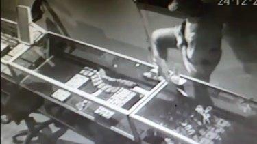 The thief kicks a jewellery cabinet.