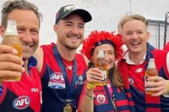 HaydenBurbank (far left), Demons player Alex Neal-Bullen and Mark Babbage (far right) inside the AFL rooms after Melbourne's win at the grand final.