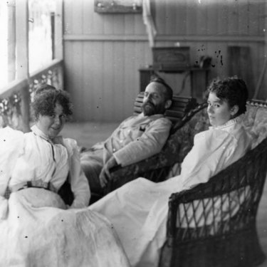 Queensland Government Electrician Edward Gustavus Campbell Barton relaxing on the verandah with two women in 1890.