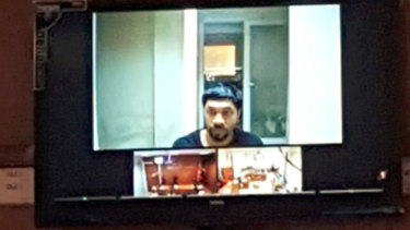 Prakash appears on a video screen during an earlier court appearance.