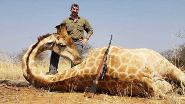 Blake Fischer poses with a giraffe he shot in Africa.