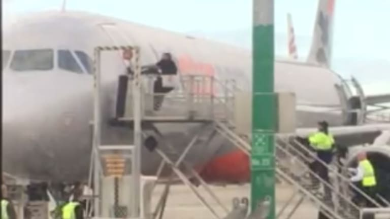 A man was arrested at Melbourne Airport on Thursday after he ran across the tarmac then tried to rip open the door of a Jetstar plane.