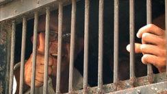 Ross Dunkley di balik jeruji besi seperti yang ditampilkan dalam film dokumenter'Dancing with Dictators: The Story of The Foreign Publisher in Burma'.