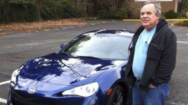 In this 2013 photo provided by Shashi Karan, Naiman poses with his new car, an unusual extravagance for him.