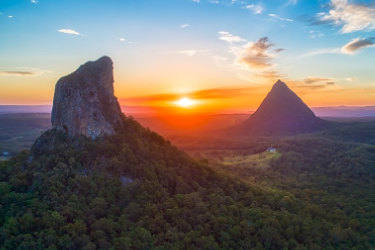 Aerial view of Mount Coonowrin in the Glasshouse National Park with Mount Beerwah in the background with the setting sun in background,Glasshouse Mountains,Sunshine Coast,Queensland,Australia traxxcoverhinterland Getty Images, downloaded as comps; if used will need to download from Getty. one time use Traveller only