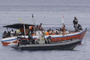 An Indonesian fishing boat filled with asylum seekers is processed by Australian authorities at Flying Fish Cove, Christmas Island.