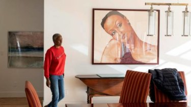 B Smith walks past a portrait of her younger self in her home.