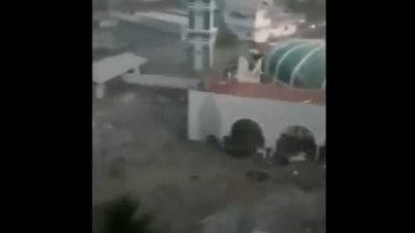 A tsunami wave floods a mosque in the town of Palu.