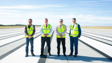Celebrating the end of the runway's construction are (from left) deputy project manager Ben Garnett, Brisbane Airport Corporation chief Gert-Jan de Graaff, project director Paul Coughlan and airport assets general manager Krishan Tangri.
