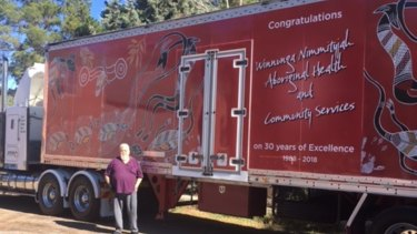 Artist Mick Huddleston with the truck he painted for Danny Palmer to help advertise the Winnunga Nimmityjah Aboriginal Health Service
