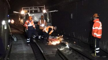 Crews work to fix the cracked track near Town Hall station on Monday morning.