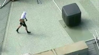 The man has a t-shirt on his head and appears to be carrying a pole.