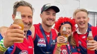 Melburnians HaydenBurbank, left, and Mark Babbage, right, pictured with Demons player Alex Neal-Bullen, were questioned by police after allegedly breaking restrictions to travel to the grand final in Perth.