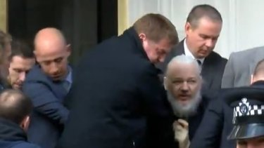Julian Assange is bundled out of the Ecuadorian embassy by London police.