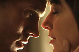 Jamie Dornan and Dakota Johnson appear in a scene from 'Fifty Shades of Grey'.