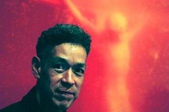 Andres Serrano in front of his controversial work, Piss Christ, that was considered by some to be blasphemous.