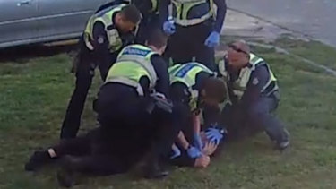 An image from CCTV footage showing police pinning pensioner John to the ground.