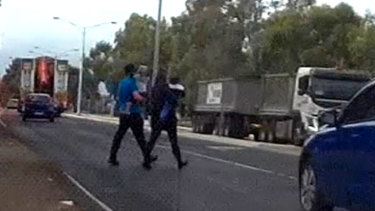 Childcare centre workers take the children back across the road.
