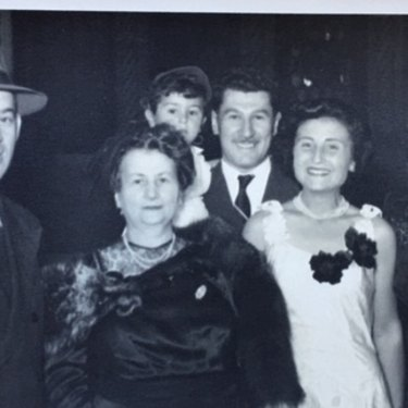 Harry Skorupa, a distant relative of Jaku's, Flore's mother Fortunee Molho, Eddie carrying Michael, Flore, and Bella Skorupa. The families lived together on arrival in Sydney and are celebrating a fellow survivor's wedding  in 1951.