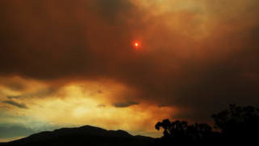 Clouds from a nearby bushfire are seen over Mount Wellington in Tasmania.