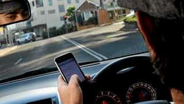 A driver illegally uses his mobile phone.