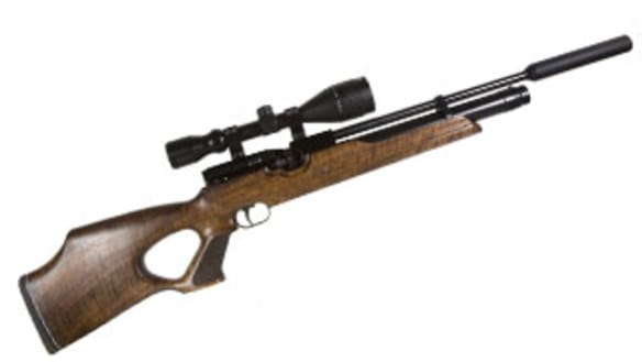 A rifle fitted with a silencer.