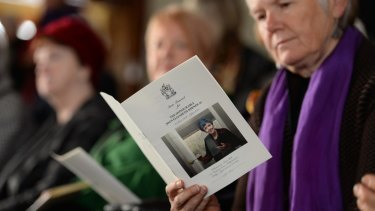 Mourners read from the order of service at the funeral for Joan Kirner.