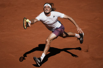 Stefanos Tsitsipas reaches for the ball against Novak Djokovic.