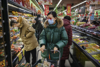 A Chinese woman wears a protective mask and sunglasses as she shops in Beijing on January 28.