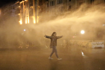 A protester is sprayed with a water cannon during the protests in Beirut.
