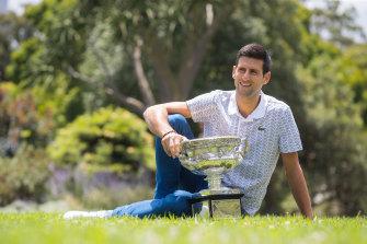 Australian Open champion Novak Djokovic poses with the trophy at the Botanic Gardens.
