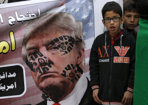 A boys next to a desecrated poster of US President Donald Trump during a rally in Islamabad, Pakistan on Sunday.