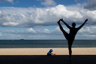 A woman exercises near St Kilda Beach.