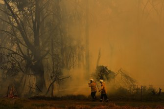 NSW RFS firefighters are surrounded by smoke as they work on battling a fire at Tahmoor, NSW.