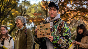 A protester holds a placard as he takes part in a Global Climate Strike protest in Tokyo on Friday.