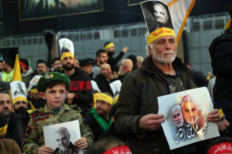 Hezbollah supporters hold pictures of slain Iranian general Qassem Soleimani during a televised speech by Hezbollah's leader Hassan Nasrallah.