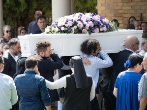 Pallbearers carry Veronique Sakr's coffin into the service.