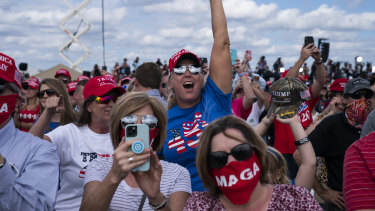 Supporters of President Donald Trump cheer as he arrives to speak at a campaign rally at Pitt-Greenville Airport in Greenville, NC.