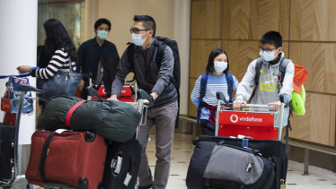 Passengers arrive at Sydney Airport on Monday wearing masks.