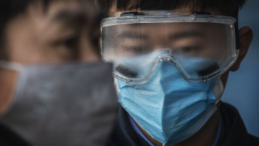 A Chinese railway worker has fogged safety goggles as he waits to check the temperature of arriving passengers a train station in Beijing.