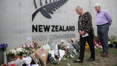 New Zealand High Commissioner Dame Annette King and husband Ray Lind view flowers left at the front gate of the high commission in Canberra on Sunday, following the mass shooting in Christchurch