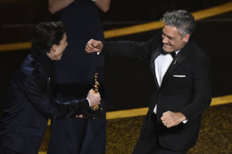 Timothee Chalamet, left, presents the award for best adapted screenplay to Taika Waititi for Jojo Rabbit.