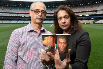 Jayant and Reva Chitnis at the MCG, holding coffee cups with an image of their missing son, Tej and his car.